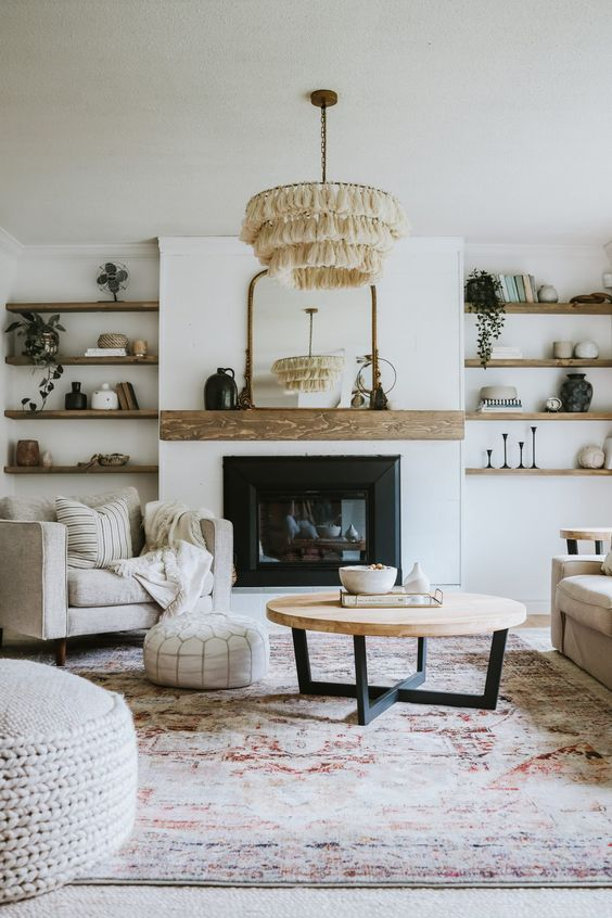 an elegant modern farmhouse living room with a built-in fireplace, built-in wooden shelves, chic neutral furniture, a tassel chandelier