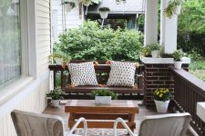 an elegant modern farmhouse porch with a dark stained suspended bench and pillows, white chairs, a wooden coffee table and potted greenery and blooms