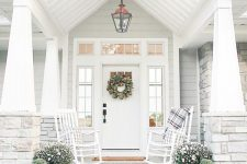 an elegant white farmhouse porch with a couple of white rockers and plaid textiles, potted blooms, candle lanterns and whitewashed pumpkins is amazing