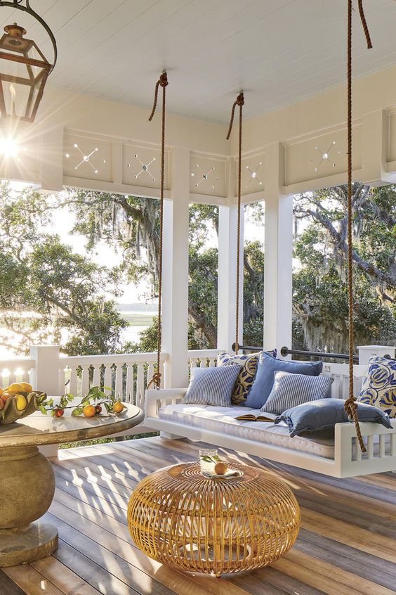 an inviting farmhouse porch with a hanging upholstered bench, a large round table, a rattan pouf and lovely textiles in blues
