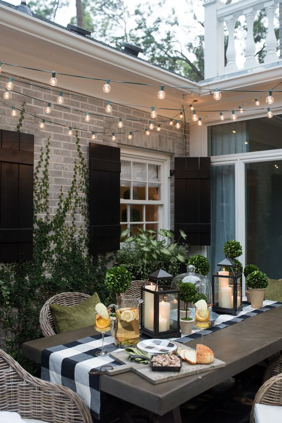an inviting modern country patio with a table and wicker chairs, muted color pillows, potted greenery and candle lanterns plus lights over the space