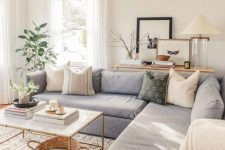 an organic modern country living room with a grey sectional, a coffee table, a basket, some plants and cool pillows