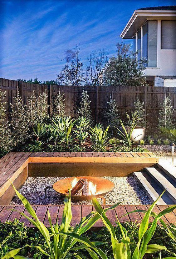 an outdoor sunken fire pit with gravel around and a deck that doubles as a bench around the pit is a cool modern solution