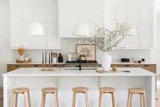 02 a beautiful millennial kitchen in two tones, light stained and white, a large kitchen island, wooden stools and white pendant lamps