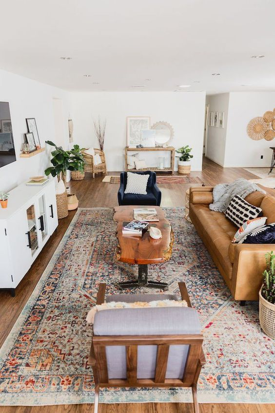 a stylish mid-century modern farmhouse living room with a leather sofa, elegant chairs, a living edge table, potted plants