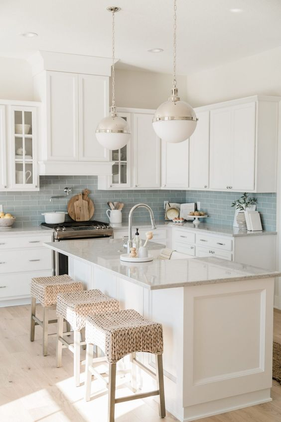 a lovely modern coastal kitchen with white cabinets, a blue subway tile backsplash, woven stools and elegant bubble pendant lamps