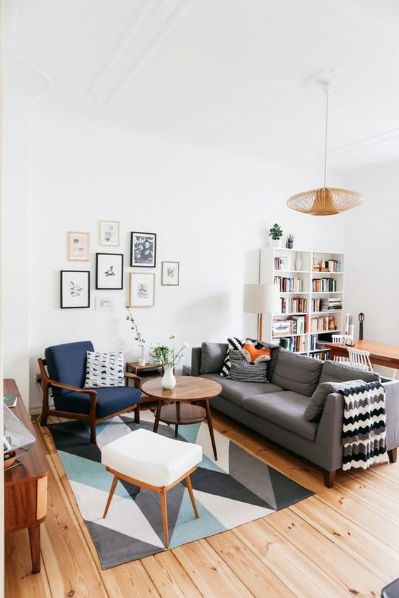 a mid-century modern living room with a bold printed rug, a grey sofa, a navy chair and a white stool, a cool gallery wall