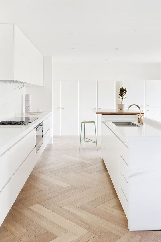a minimalist white kitchen with sleek cabinets, a chevron floor and a butcherblock countertop, gold fixtures is a cool idea