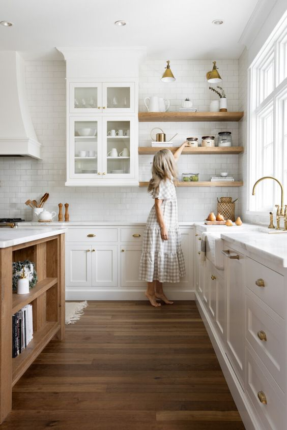 a cozy modern kitchen with white cabinets, light stained shelves, a light stained kitchen island, brass sconces and fixtures is chic