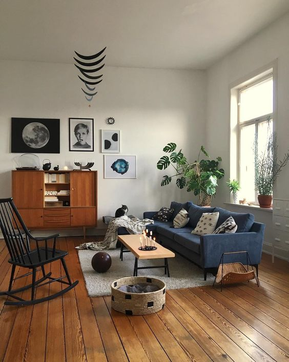 a mid-century modern living room with a navy sofa, a black rocker, potted plants, a stylish gallery wall and some cat furniture
