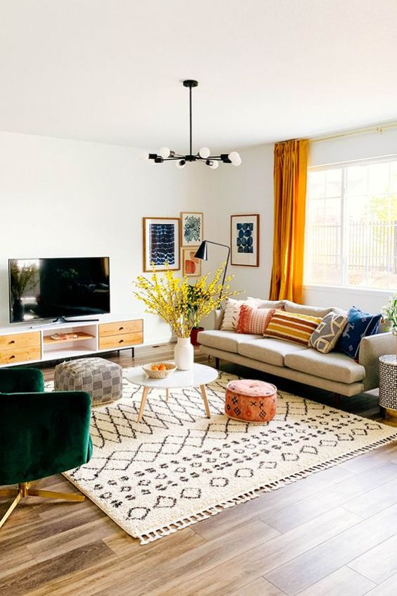 a bright mid-century modern living room with a comfy sofa, a green chair, a TV unit, printed textiles and a bright gallery wall