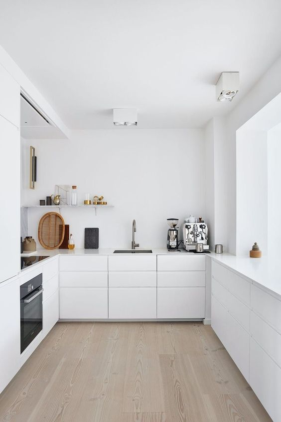 a minimalist white kitchen with sleek cabinets, sleek countertops, a shelf and built-in appliances is a chic space