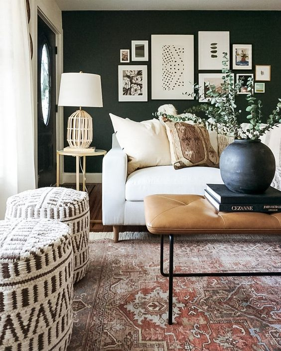 a chic black and white modern boho living room with a black accent wall, a white sofa, printed poufs, a leather ottoman and a cool gallery wall