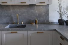 08 a modern grey kitchen with a grey marble backsplash and countertops, brass fixtures is a very chic and bold solution