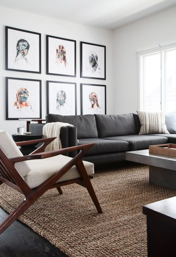 an elegant mid-century modern living room with a grey sofa, a concrete table, a white chair, a bright portrait gallery wall