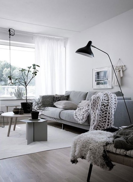 a dreamy Scandinavian living room in white, black and grey, with a comfy sofa, grey chairs, black accessories for more drama