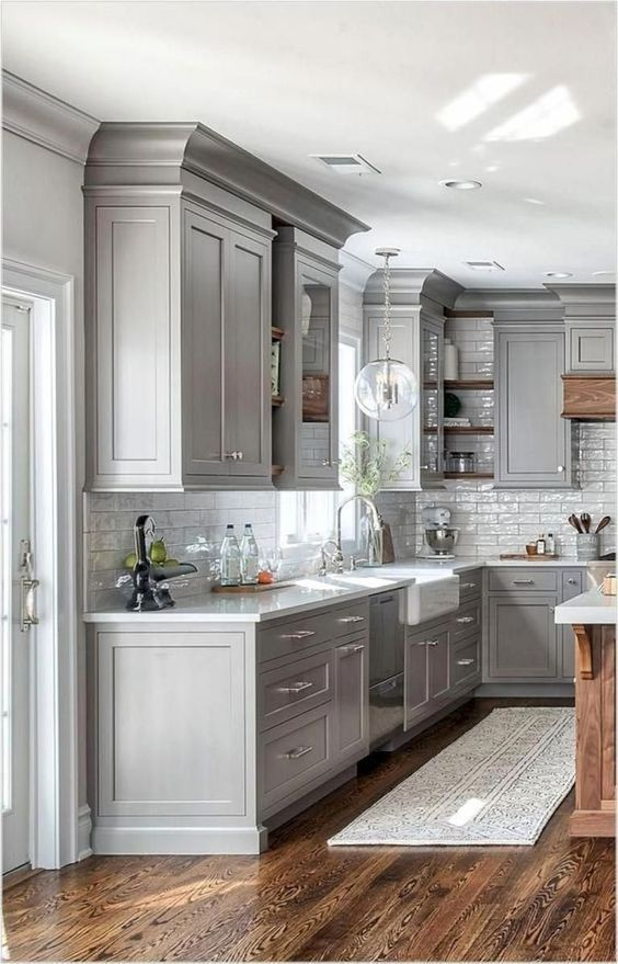 a modern farmhouse grey kitchen with white stone countertops and a white subway tile backsplash, with neutral fixtures is chic