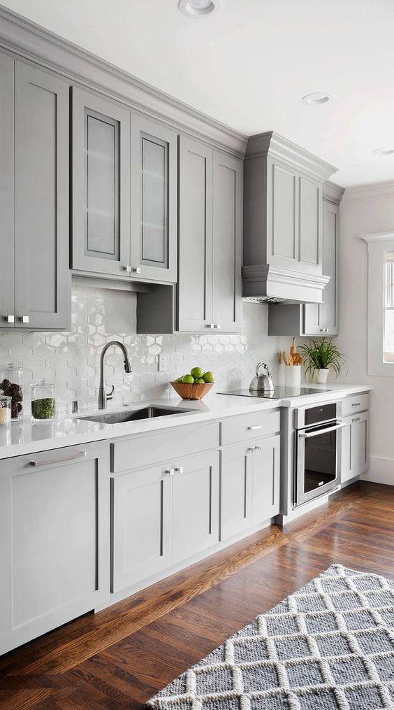 a beautiful dove grey modern farmhouse kitchen with a white Moroccan tile backsplash and white stone countertops plus neutral fixtures