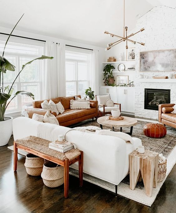 a welcoming mid-century modern living room with a built-in fireplace, a white and rust-colored sofa, a woven bench, potted plants