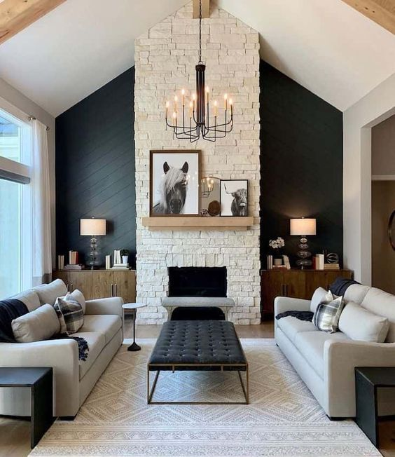 a chic living room wiht a black accent wall, a fireplace, grey sofas, black benches, a black ottoman and a vintage chandelier
