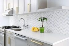 11 a glam grey kitchen with white stone countertops, a chevron tile backsplash and gold fixtures is a cool and shiny space
