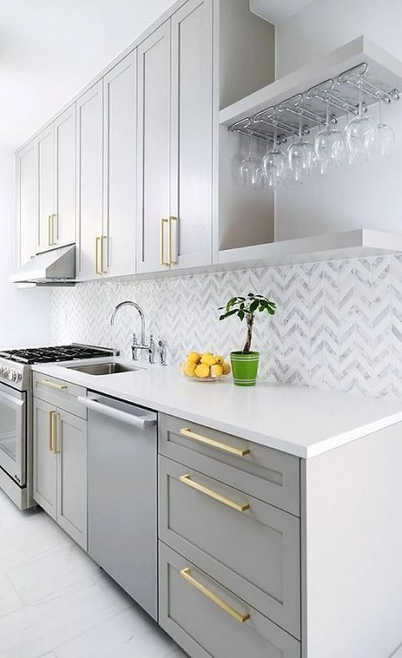 a glam grey kitchen with white stone countertops, a chevron tile backsplash and gold fixtures is a cool and shiny space