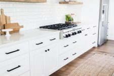 12 a cozy white modern farmhouse kitchen with a white subway tile backsplash, touches of natural wood and black fixtures