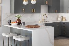 13 a refined kitchen with grey cabinets, a large kitchen island with a waterfall countertop, brass fixtures and gold pendant lamps