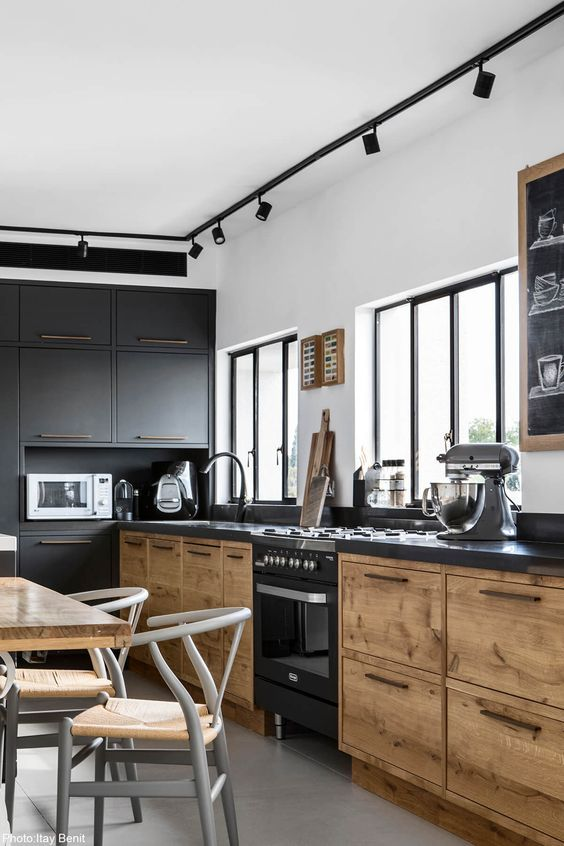 a modern industrial kitchen with metal and wooden cabinets, metal countertops, spotlights and a dining zone right here