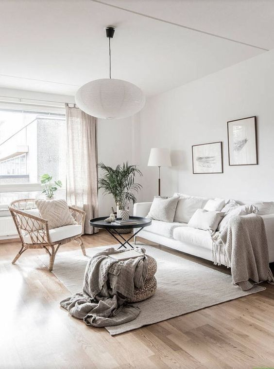 a neutral living room with a white sofa, a rattan chair, neutral textiles, potted greenery and a delicate gallery wall
