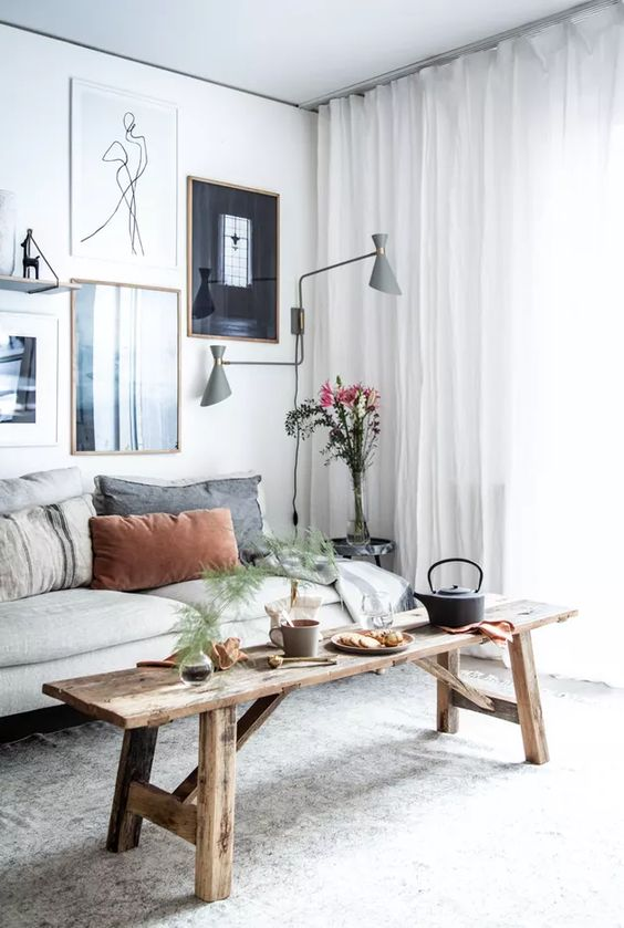a Scandinavian living room with a neutral sofa, a wooden bench, a lovely gallery wall and grey sconces is chic