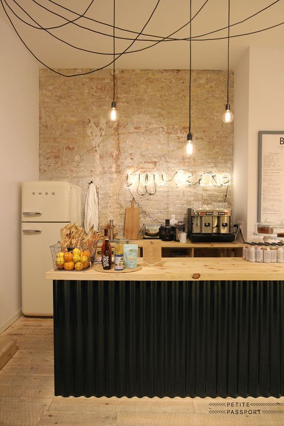 an industrial kitchen with a brick accent wall, a black kitchen island with a butcherblock countertops and wooden cabinets plus bulbs
