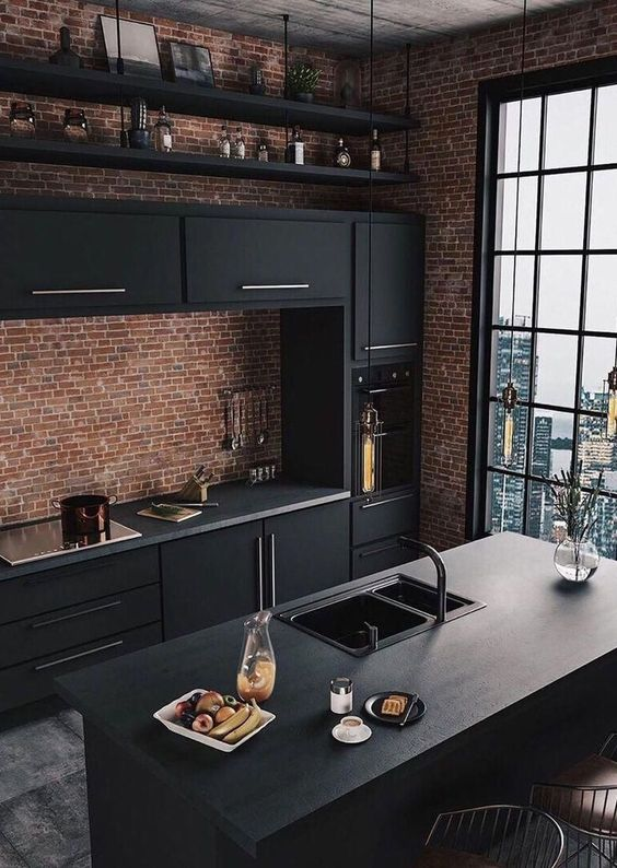 a fantastic industrial kitchen with red brick walls, black metal cabinets, concrete countertops and bulbs hanging over the space