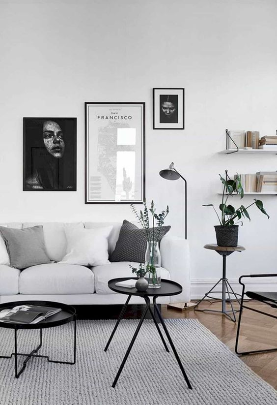 a laconic living room in Scandi style, with a white sofa, open shelves, black tables and a chair, black and white gallery wall