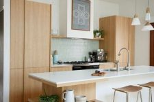 17 a serene Scandinavian kitchen with light stained cabinets, a large kitchen island with open shelves, a blue tile backsplash and plywood stools