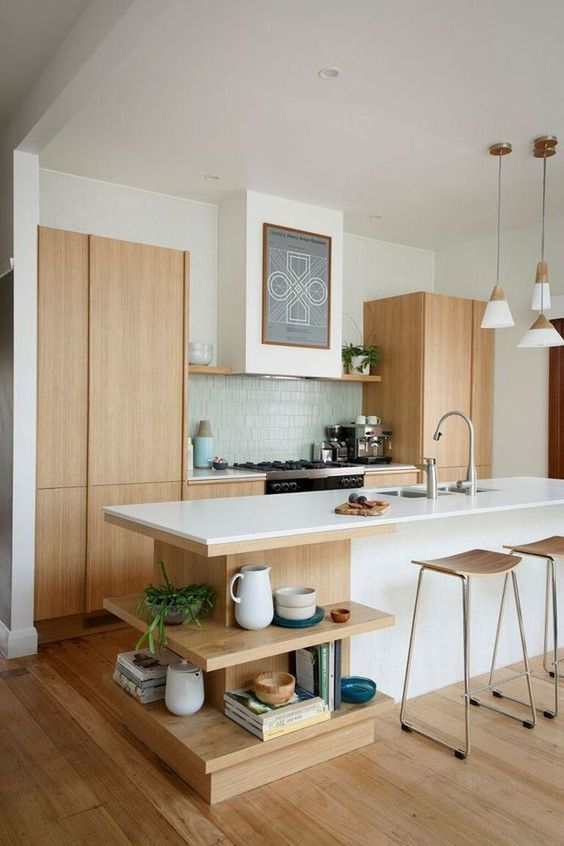 a serene Scandinavian kitchen with light stained cabinets, a large kitchen island with open shelves, a blue tile backsplash and plywood stools