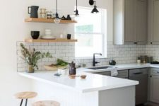 19 a lovely modern kitchen with grey cabinets, a white kitchen island, a white subway tile backsplash, open shelves and touches of black