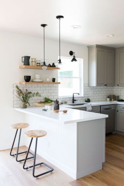 a lovely modern kitchen with grey cabinets, a white kitchen island, a white subway tile backsplash, open shelves and touches of black
