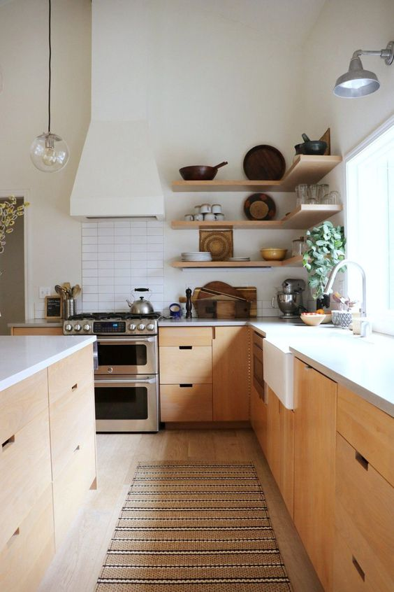 a contemporary kitchen with light stained cabinets, open shelves, white stone countertops, a hood and a pendant lamp