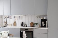 21 a modern grey kitchen with sleek cabinets, a white tile backsplash, a small table and woven chairs plus a striped rug