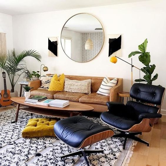 a stylish mid-century modern living room with a leather sofa, a lovely oval coffee table, a black lounger