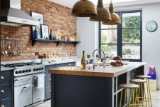 22 a chic kitchen with navy cabinets, a red brick wall, a navy kitchen island with a butcherblock countertop, metal pendant lamps