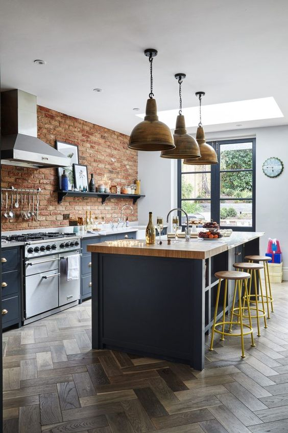 a chic kitchen with navy cabinets, a red brick wall, a navy kitchen island with a butcherblock countertop, metal pendant lamps