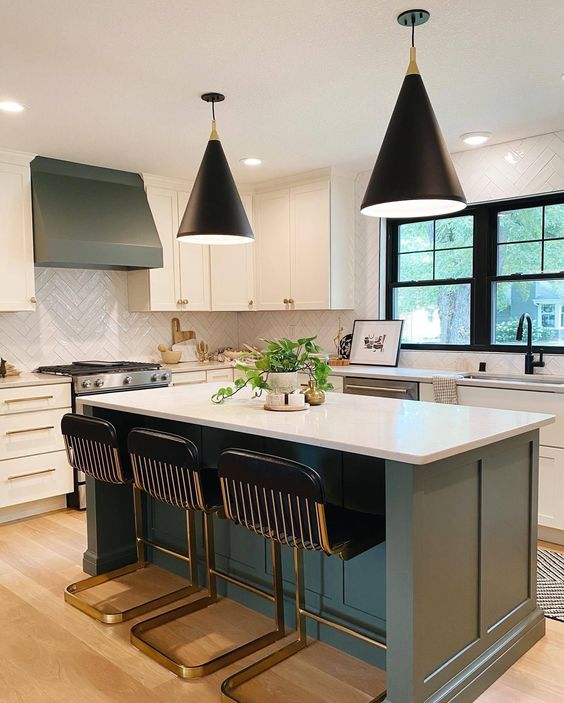 a chic modern kitchen with white and grey cabinets, a white chevron tile backsplash, black stools and black pendant lamps