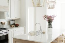 24 an elegant modern farmhouse kitchen with white cabinets, a light stained kitchen island, gold pendant lamps and woven chairs
