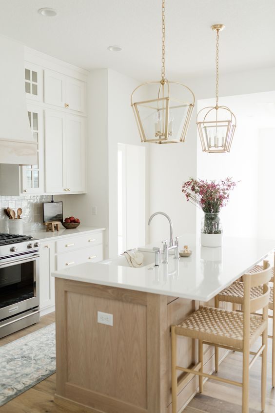 an elegant modern farmhouse kitchen with white cabinets, a light stained kitchen island, gold pendant lamps and woven chairs