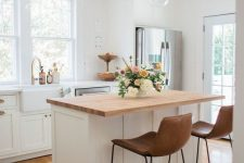 25 a pretty white farmhouse kitchen with shaker style cabinets, a small kitchen island with a butcherblock countertop and leather stools