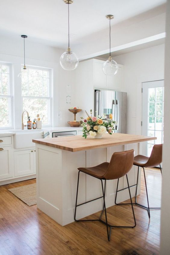 a pretty white farmhouse kitchen with shaker style cabinets, a small kitchen island with a butcherblock countertop and leather stools