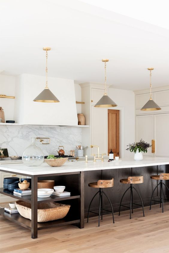 a chic farmhouse kitchen with white shaker style cabinets, a dark stained kitchen island with open shelves, grey pendant lamps