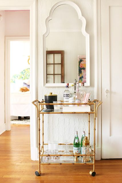 an elegant gold bamboo bar cart is a stylish addition and a must for a millennial living room